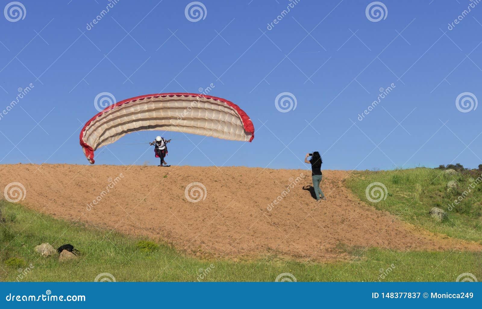 Kvinnlig paragliderpilot som tar av, och kvinna som filmar med hennes mobil