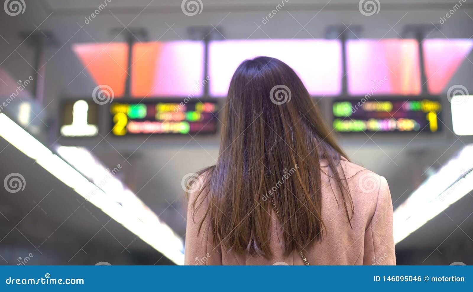 Kvinnlig pendlare som ser schema p? j?rnv?gsstationen som ?r turist- i ny stad