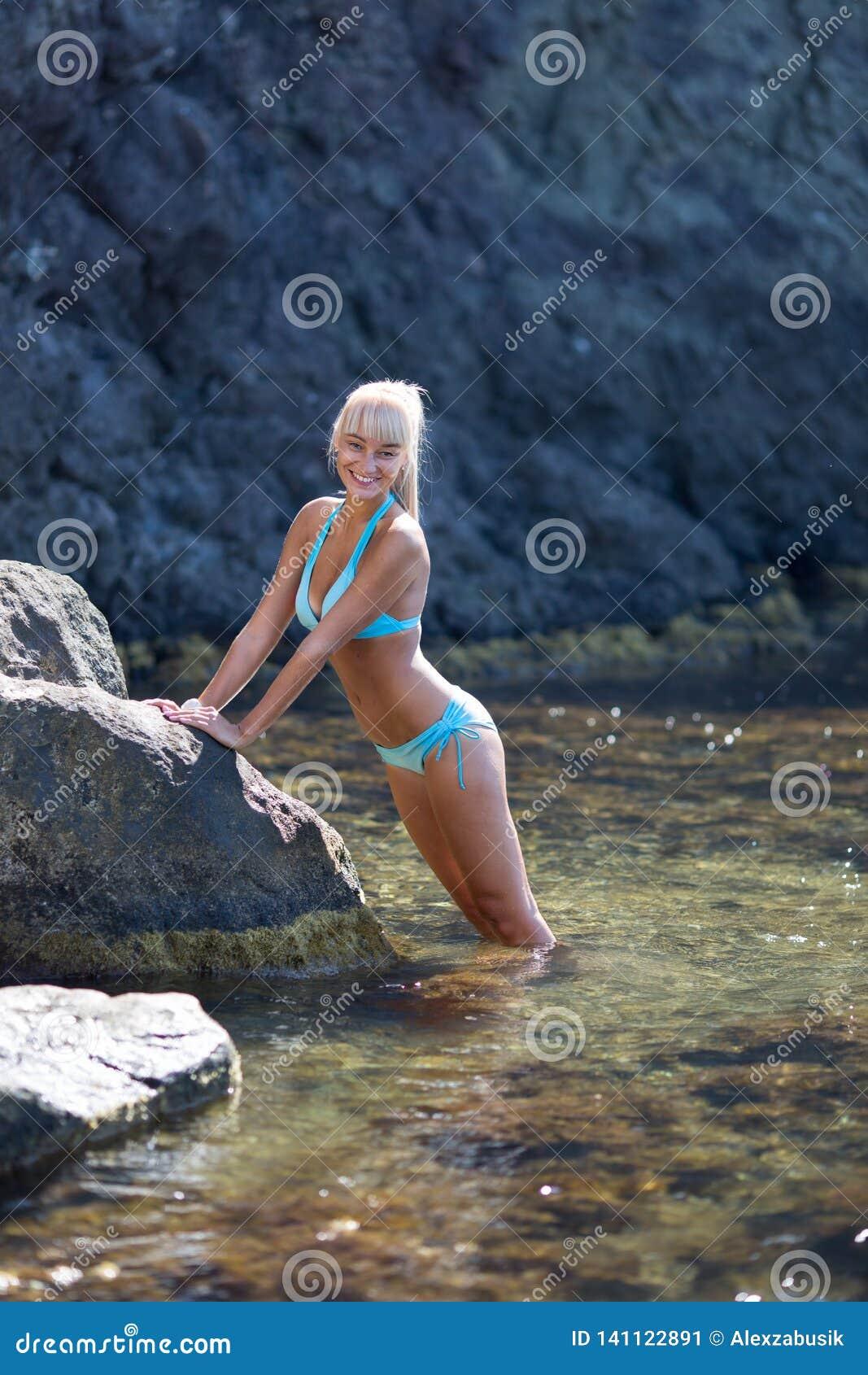 Kvinnlig person som vilar på det avskilda stället av den lösa steniga kusten