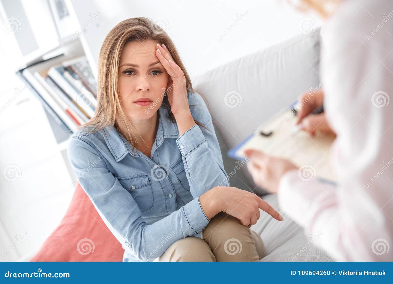 Kvinnlig psychologystterapiperiod med klienten som sitter inomhus den fundersamma flickan