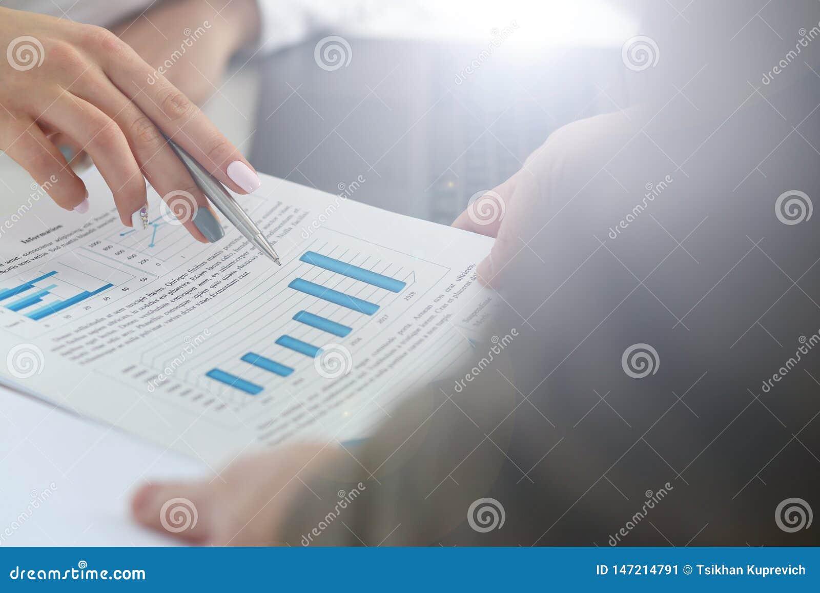 Kvinnlig punkt f?r penna f?r silver f?r arminnehav i finansiell graf