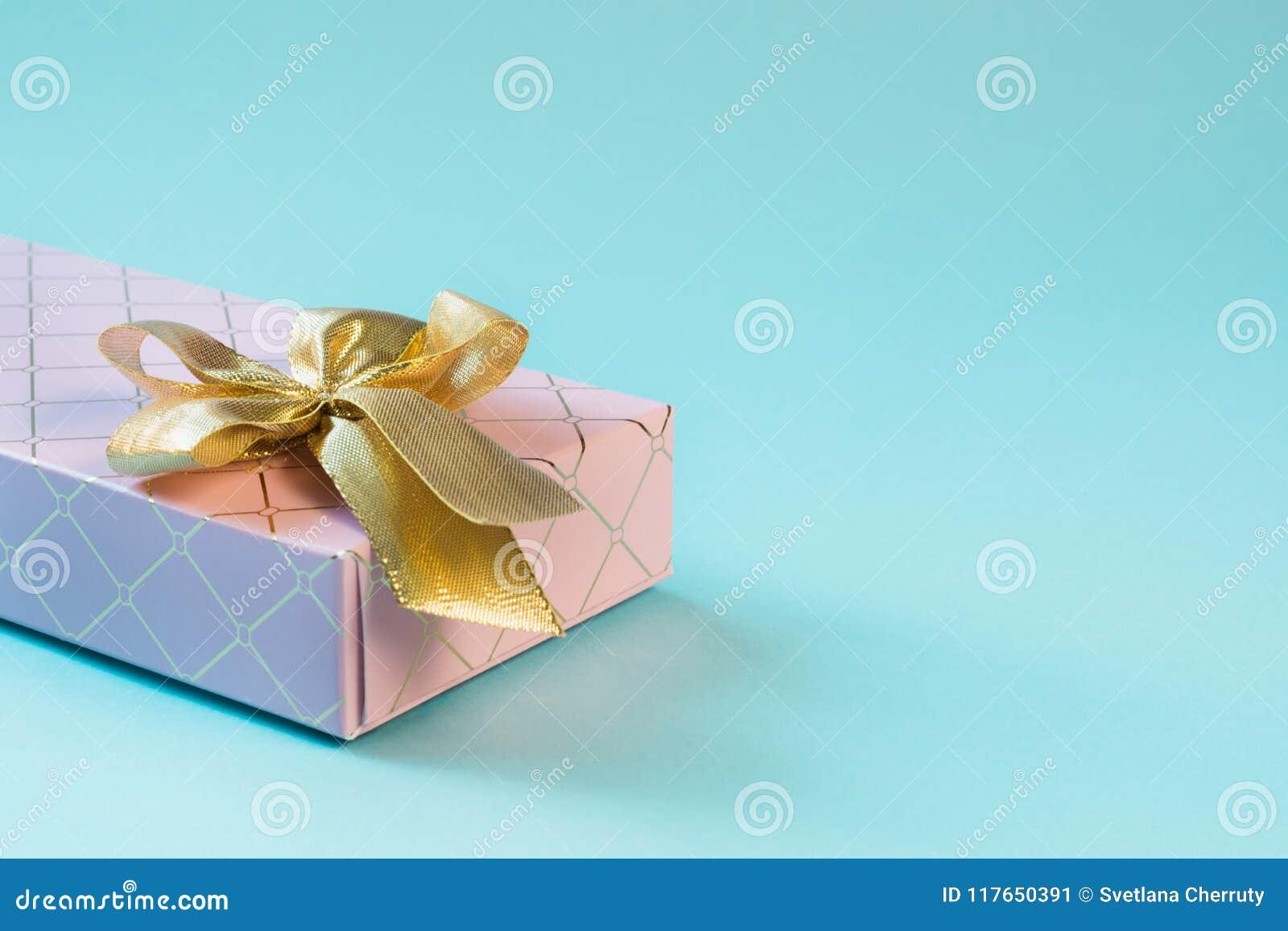 Kvinnlig rosa gåvaask med det guld- bandet på punchy pastellblått Födelsedag kopiera avstånd