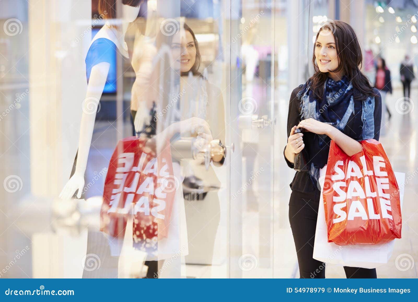 Kvinnlig shoppare med Sale påsar i shoppinggalleria