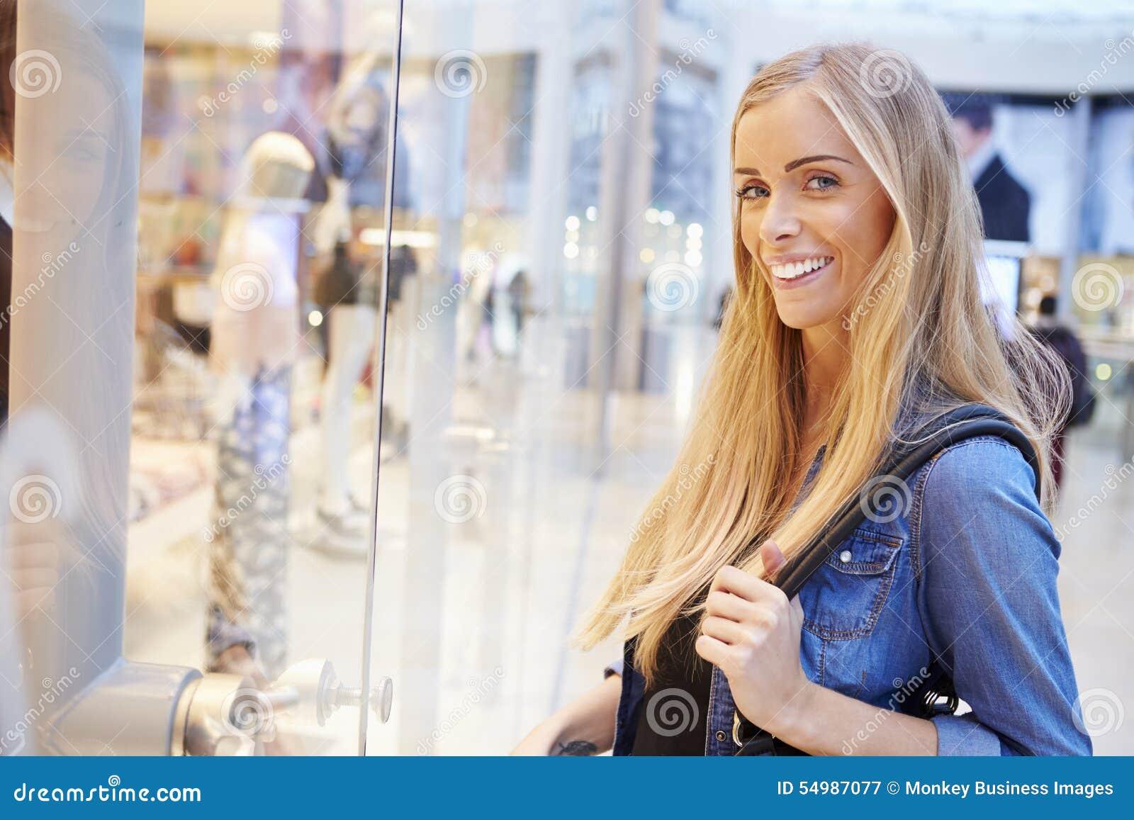 Kvinnlig shoppare som ser i lagerfönster inom shoppinggalleria