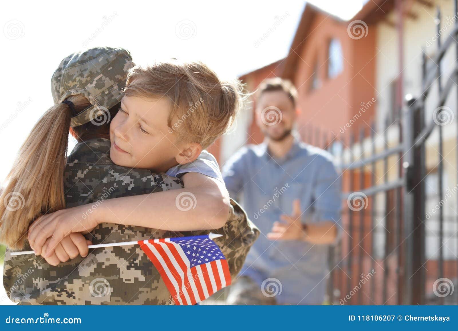 Kvinnlig soldat med hennes son utomhus Militärtjänst