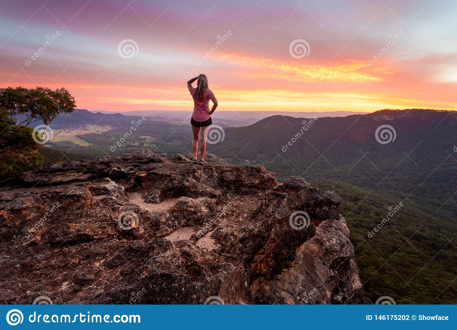 Kvinnlig som håller ögonen på solnedgången efter en lång dag som fotvandrar i blåa berg