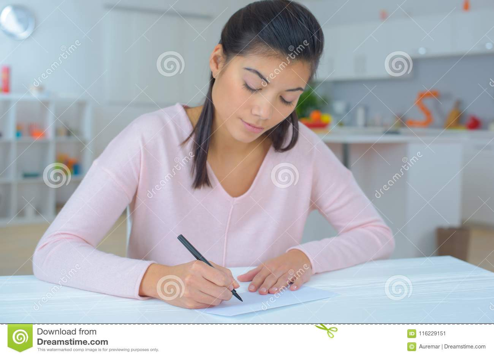 Kvinnlig som skrivar ett brev