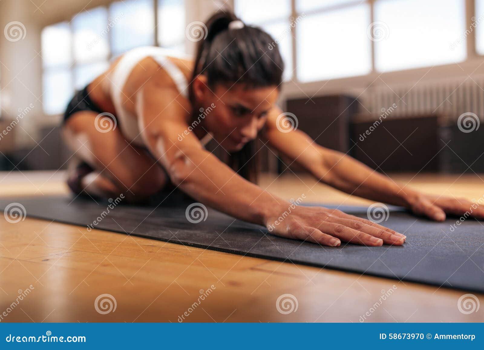 Kvinnlig som utför yoga på övningen som är matt på idrottshallen