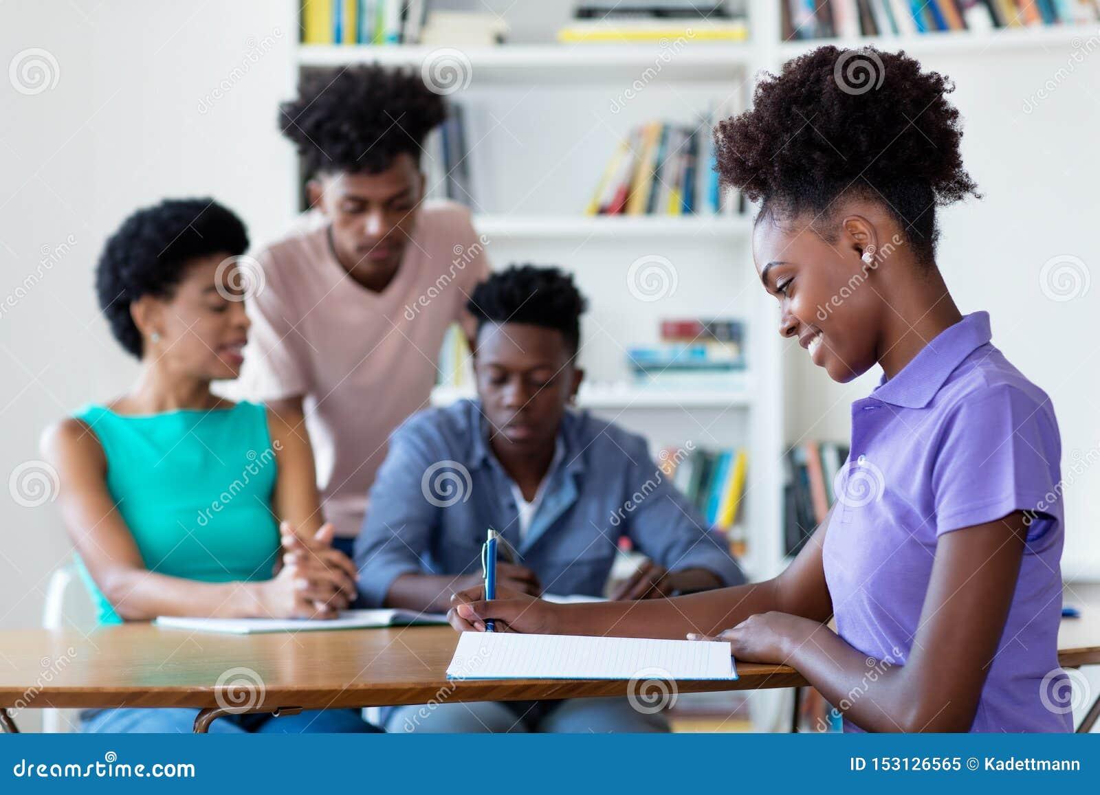 Kvinnlig student för ung afrikansk amerikan som lär på skrivbordet på skola