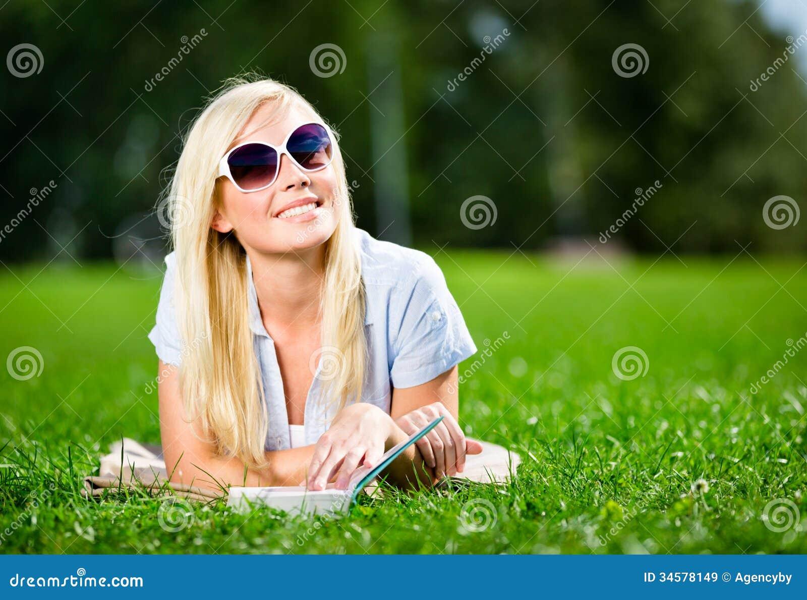 Kvinnlig student i solglasögon med boken på gräset