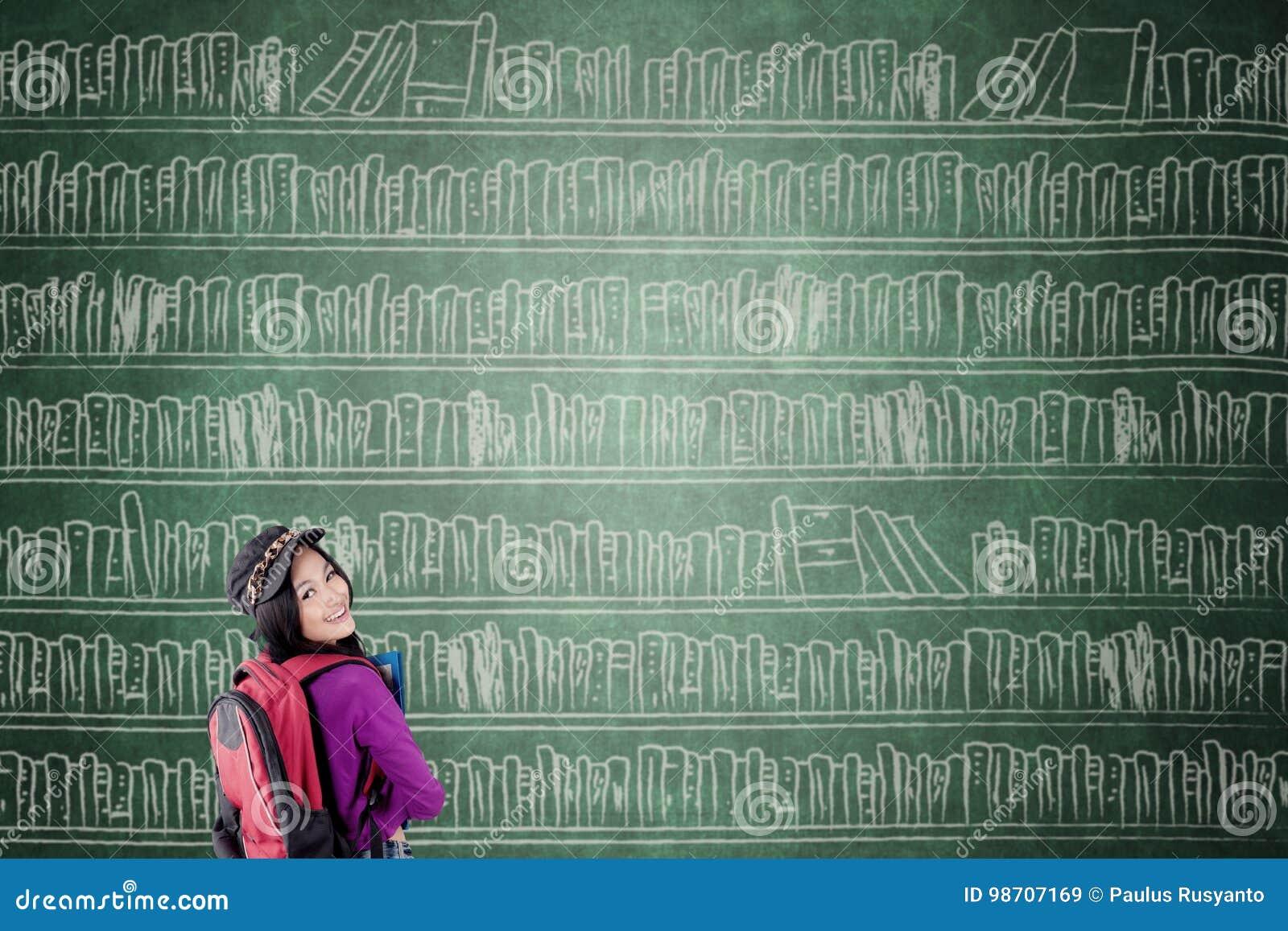 Kvinnlig student med den stora bokhyllan