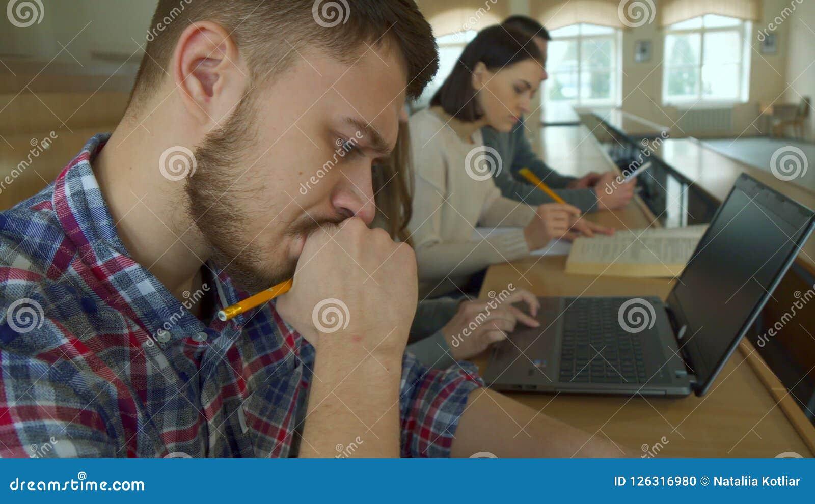 Kvinnlig student som använder bärbara datorn på hörsalen