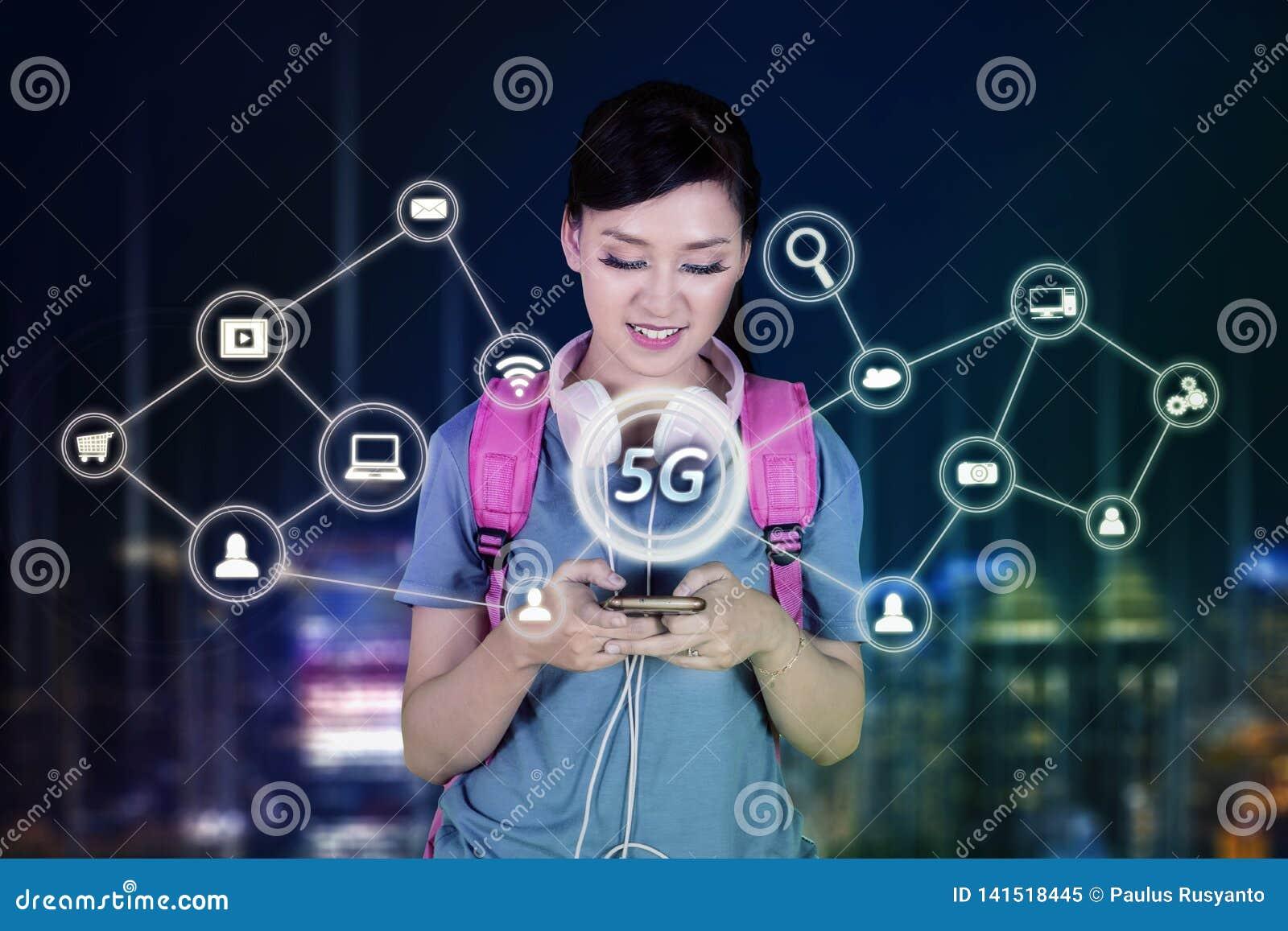 Kvinnlig student som använder en telefon med nätverket 5G