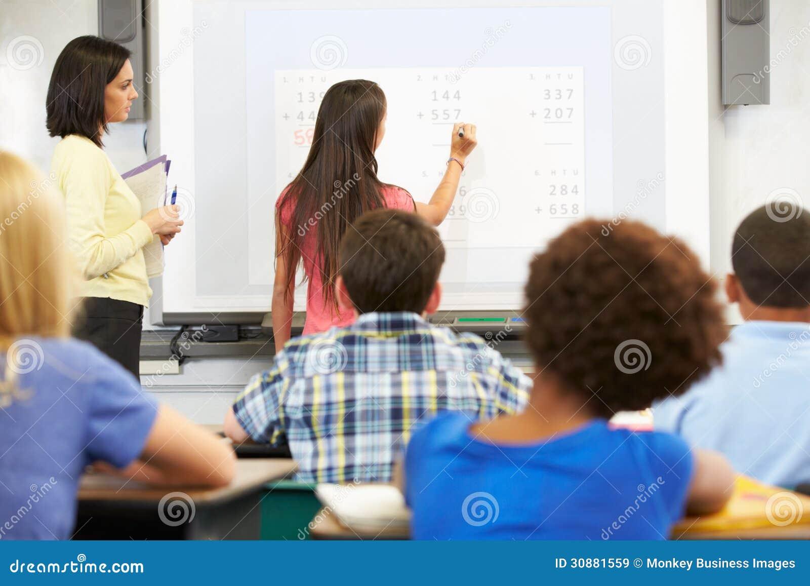 Kvinnlig student Writing Answer On Whiteboard