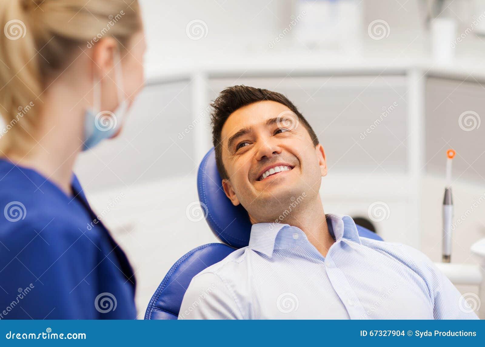 Kvinnlig tandläkare med den lyckliga manliga patienten på kliniken
