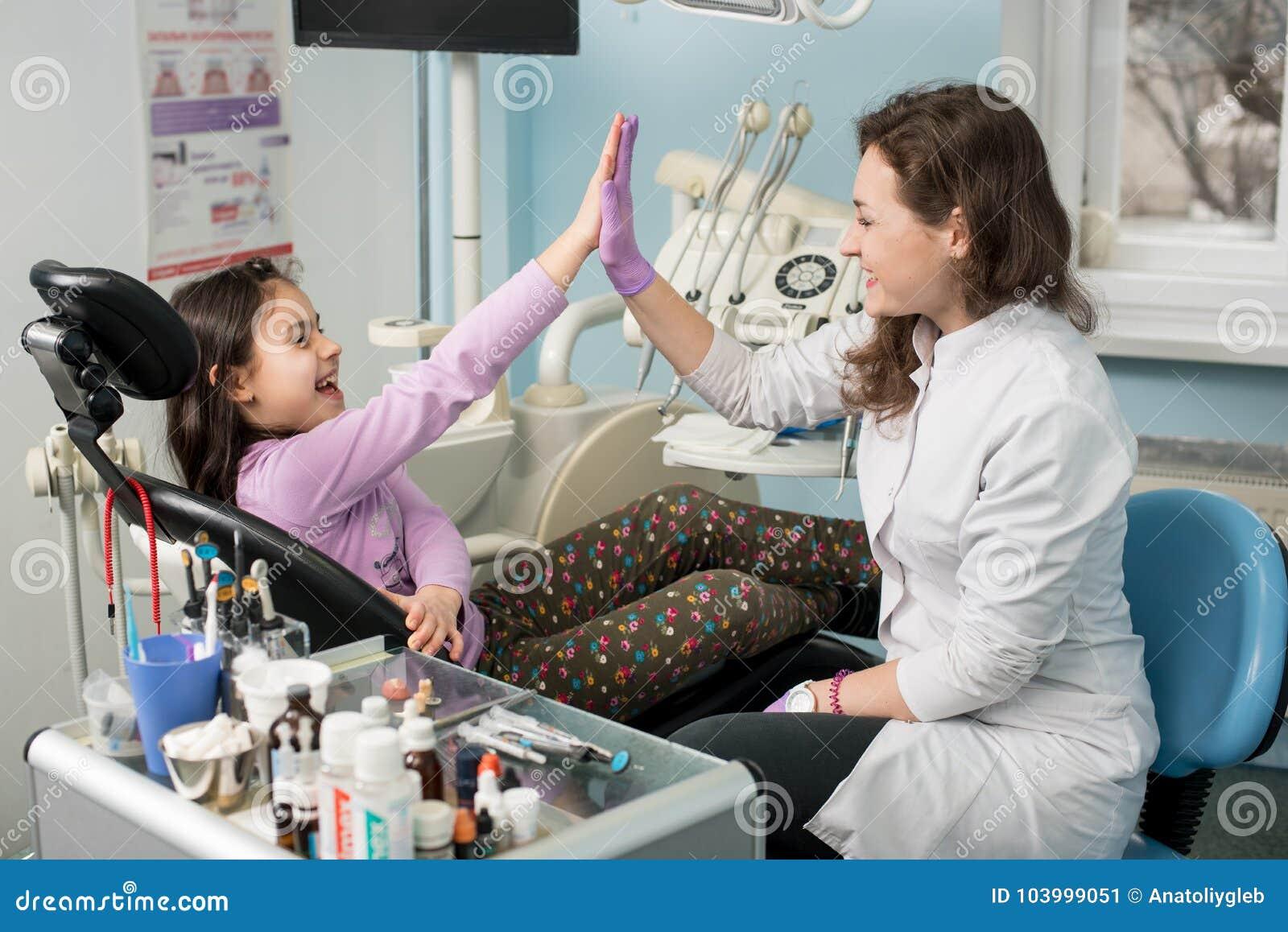 Kvinnlig tandläkare- och flickapatient som tillfredsställs, når behandling av tänder på det tand- klinikkontoret, att ha lett och