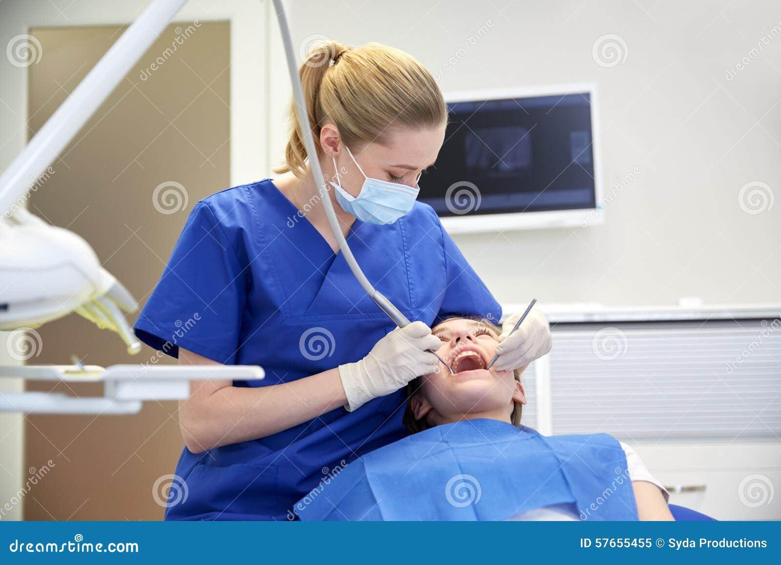 Kvinnlig tandläkare som kontrollerar tålmodiga flickatänder