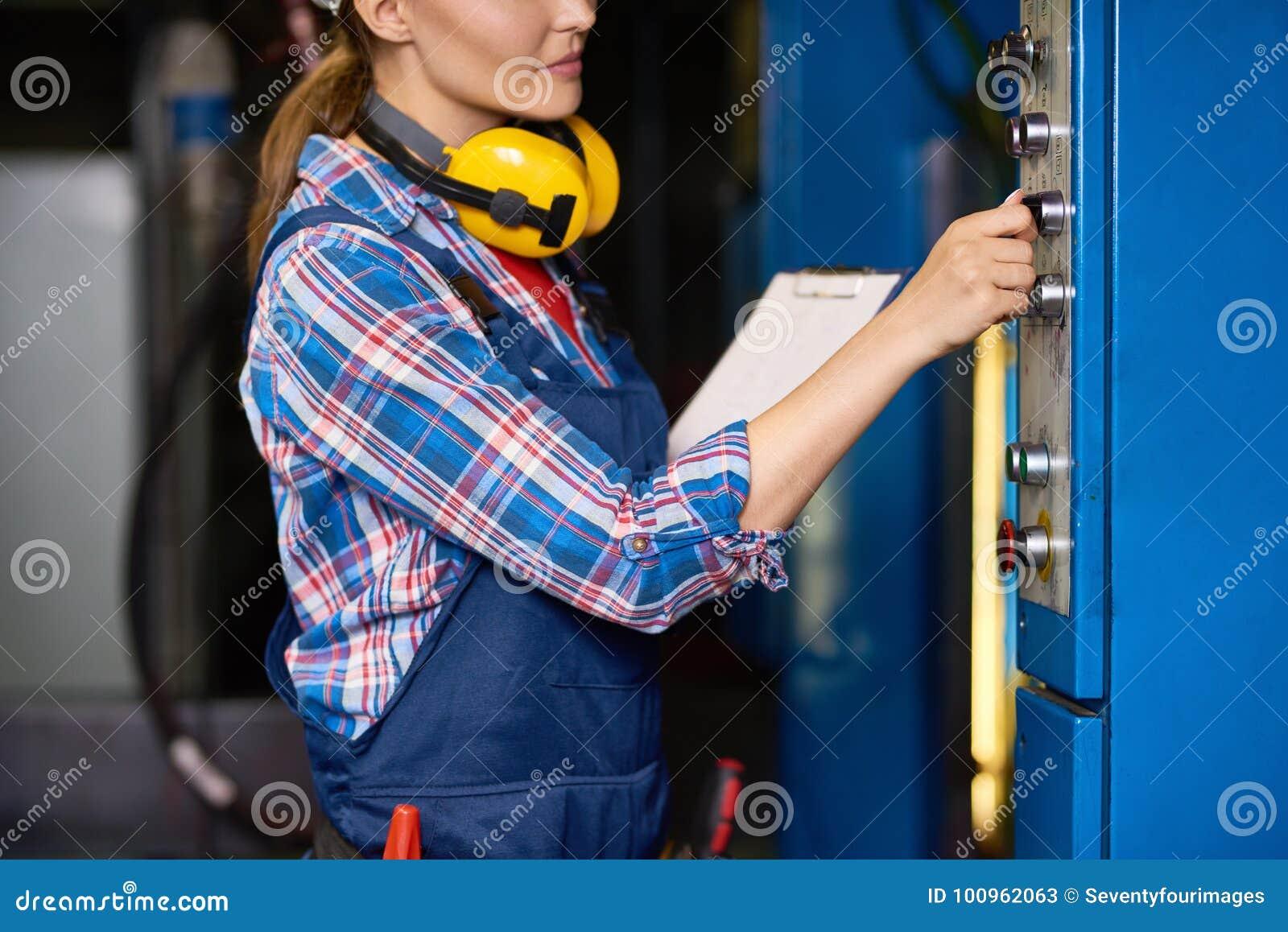 Kvinnlig tekniker Operating Machines på fabriken