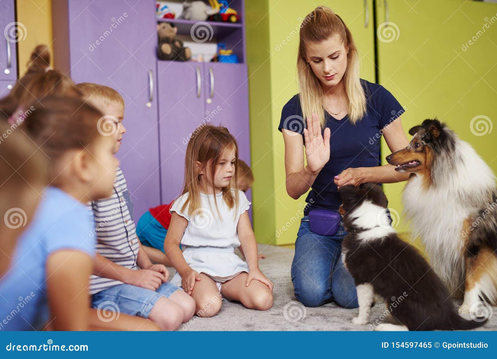 Kvinnlig terapeut och hennes hund som spelar med barn