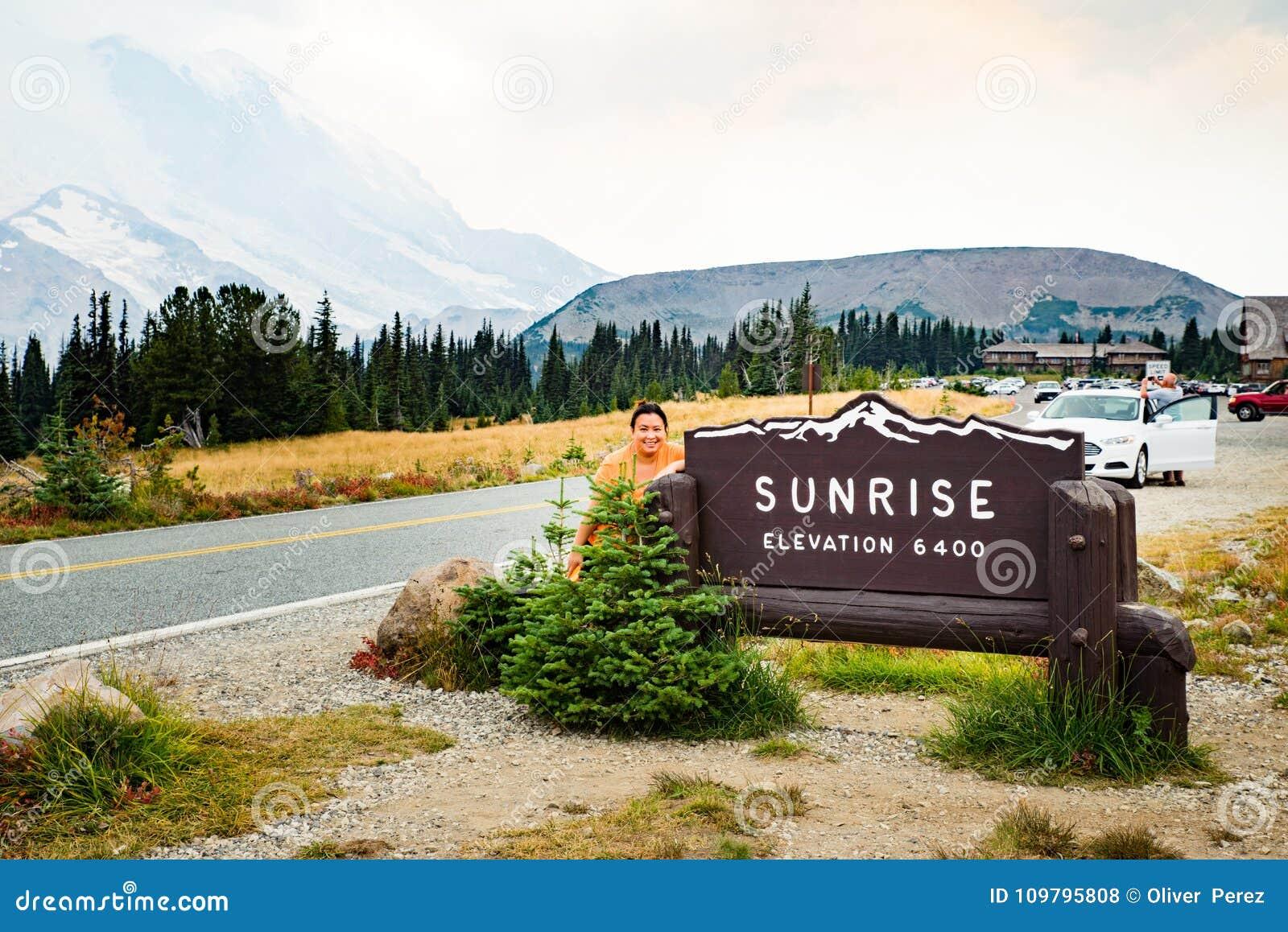 Kvinnlig turist- besöka Mt som är mer regnig på soluppgångbesökaremitten