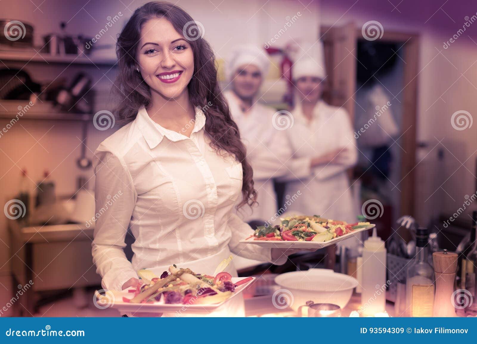 Kvinnlig uppassare som tar maträtten på kök