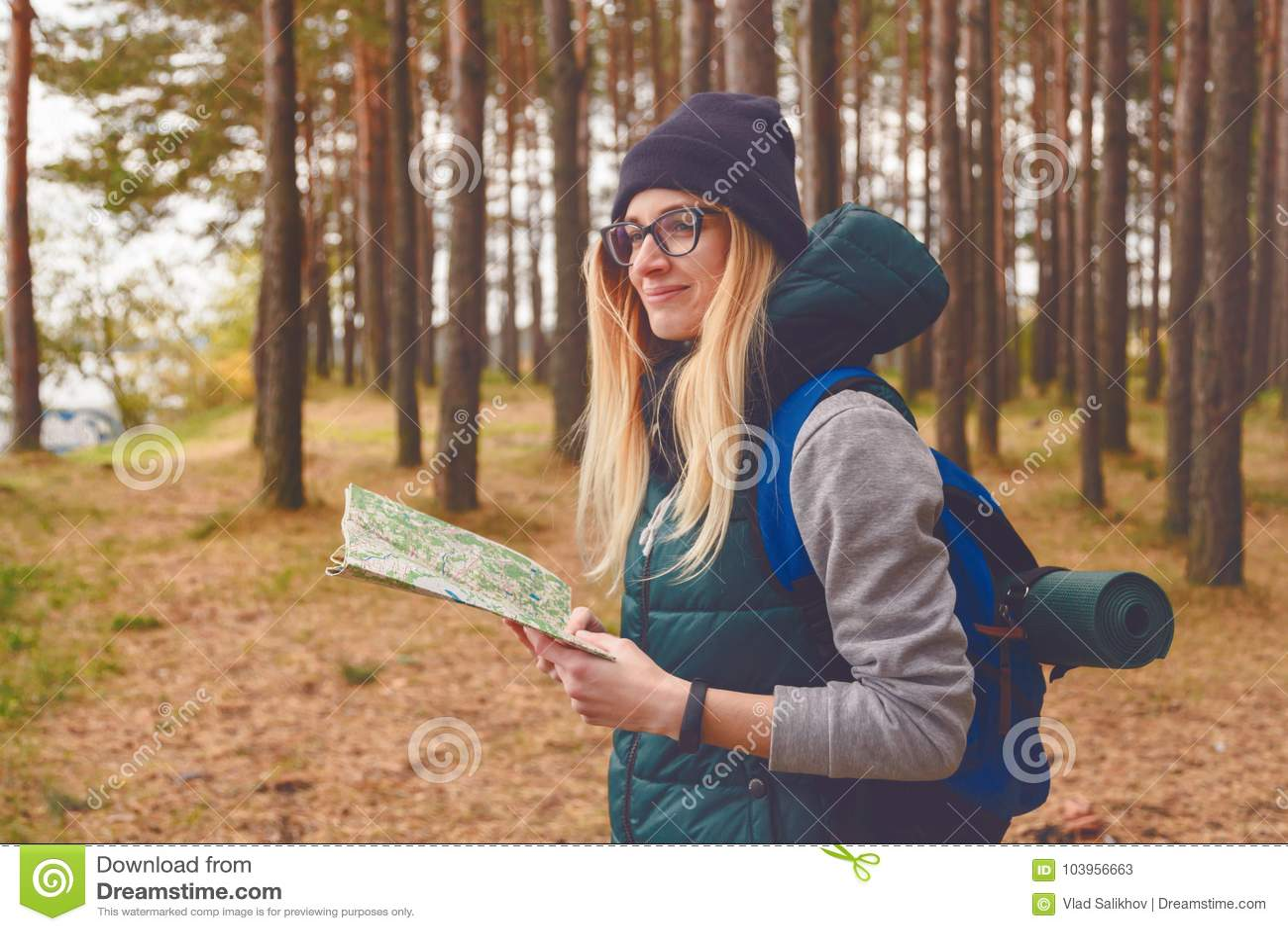 Kvinnlig utforskare med översikten som är utomhus- i skogen i höst