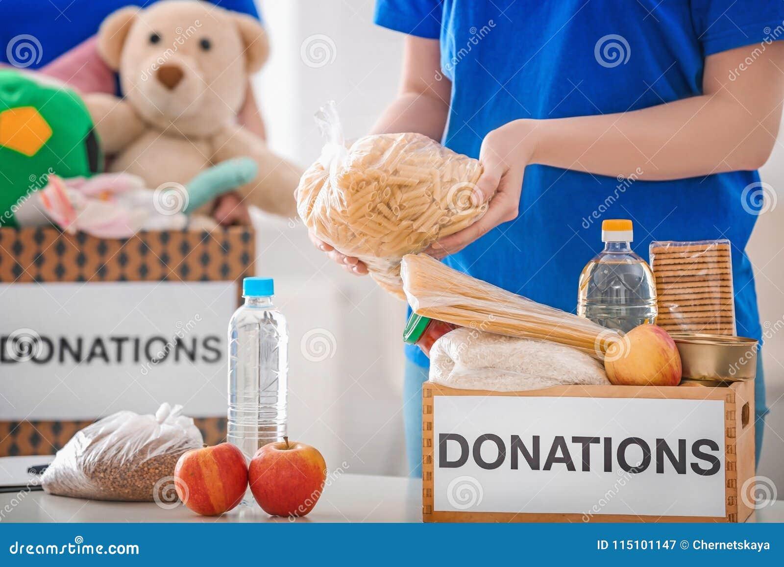 Kvinnlig volontär som sätter livsmedelsprodukter i donationask