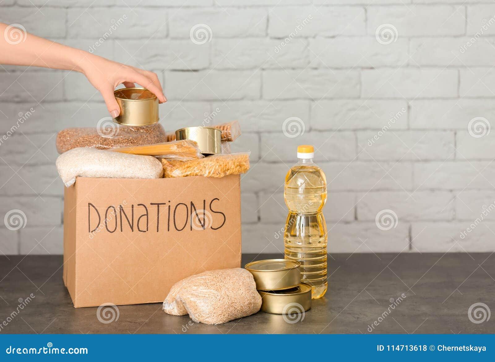 Kvinnlig volontär som sätter mat in i donationasken