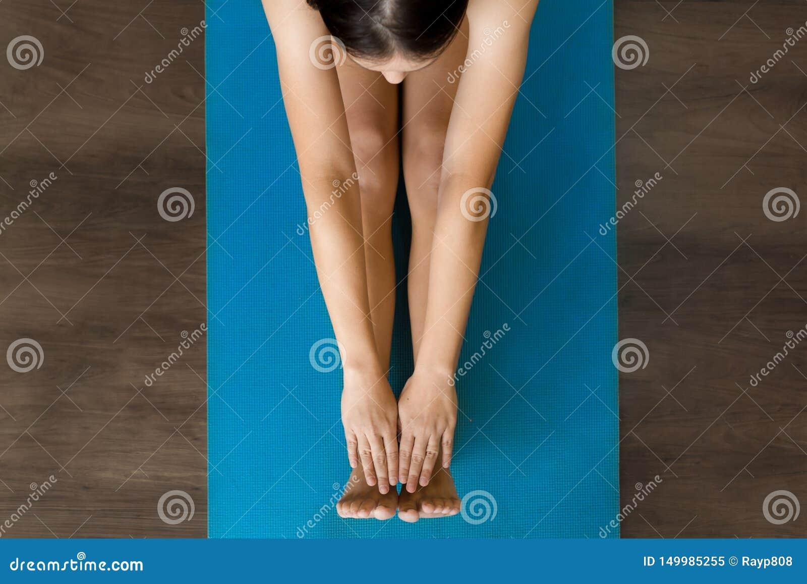 Kvinnlig vuxen människa som sträcker på en yoga som är matt i grupp
