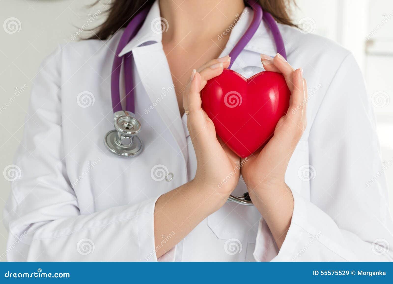 Kvinnliga doktorers händer som rymmer röd hjärta