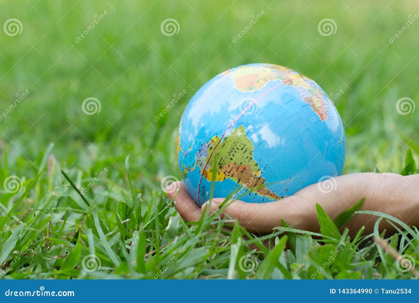 Kvinnliga händer som rymmer att sväva jord på naturlig grön bakgrund brown räknad dagjord som miljölövverk går den gående gröna t