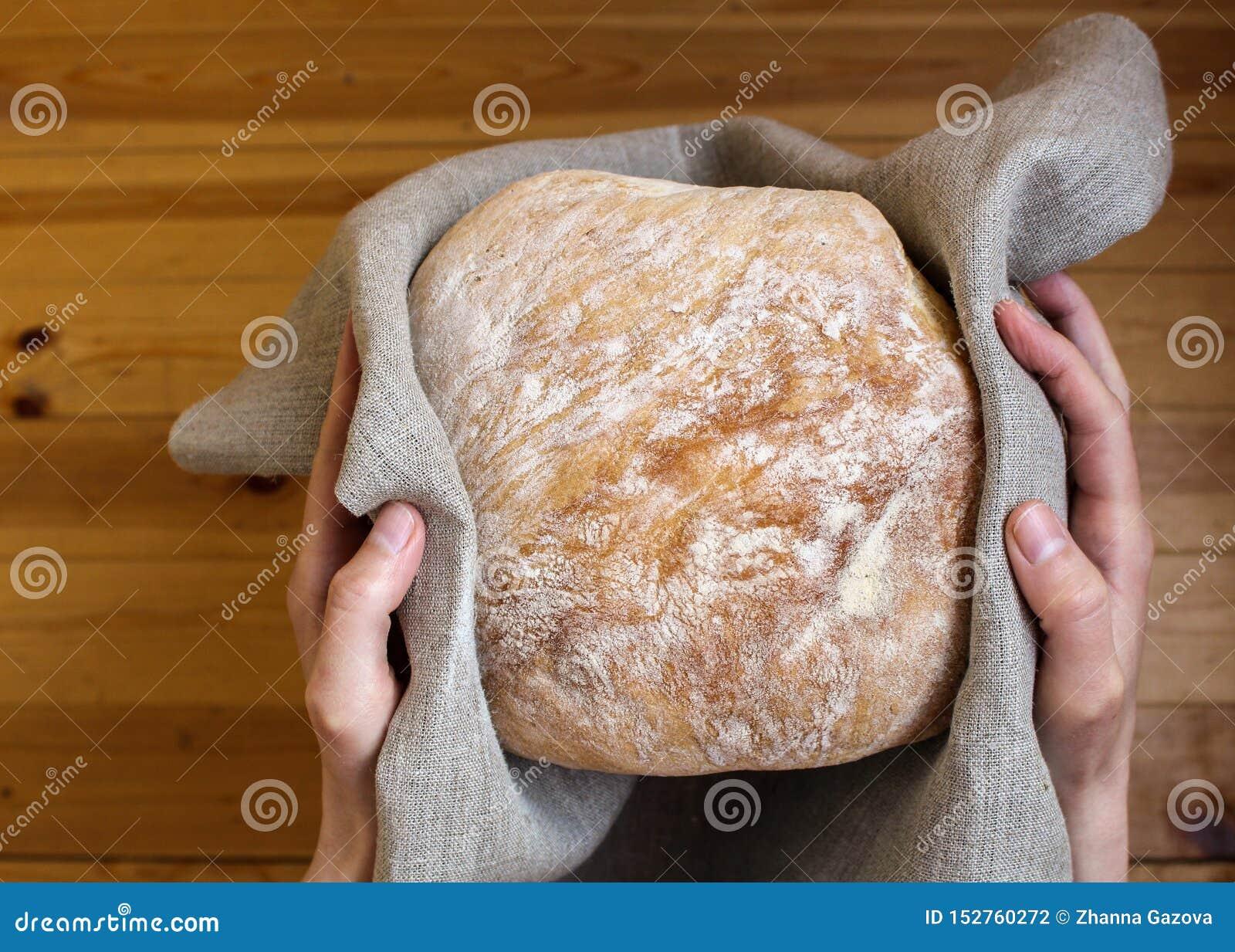 Kvinnliga händer som rymmer bröd i linnetyg