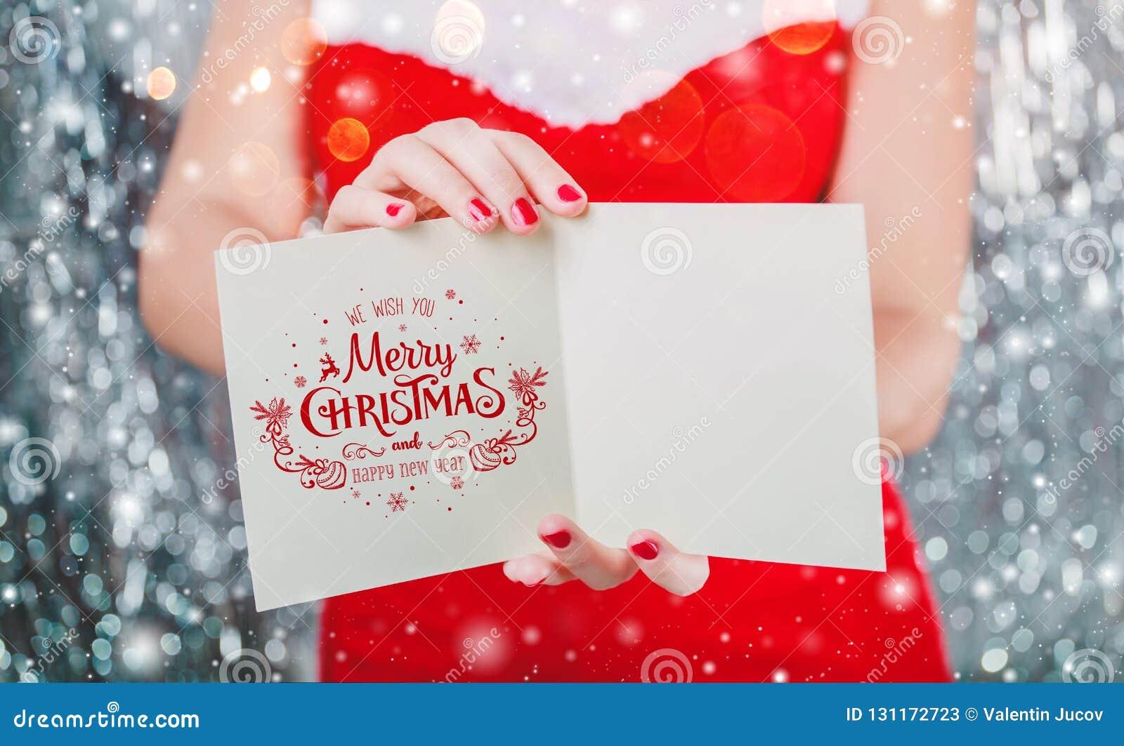Kvinnliga händer som rymmer den glade julkortet eller bokstaven till jultomten Tema för Xmas och för nytt år