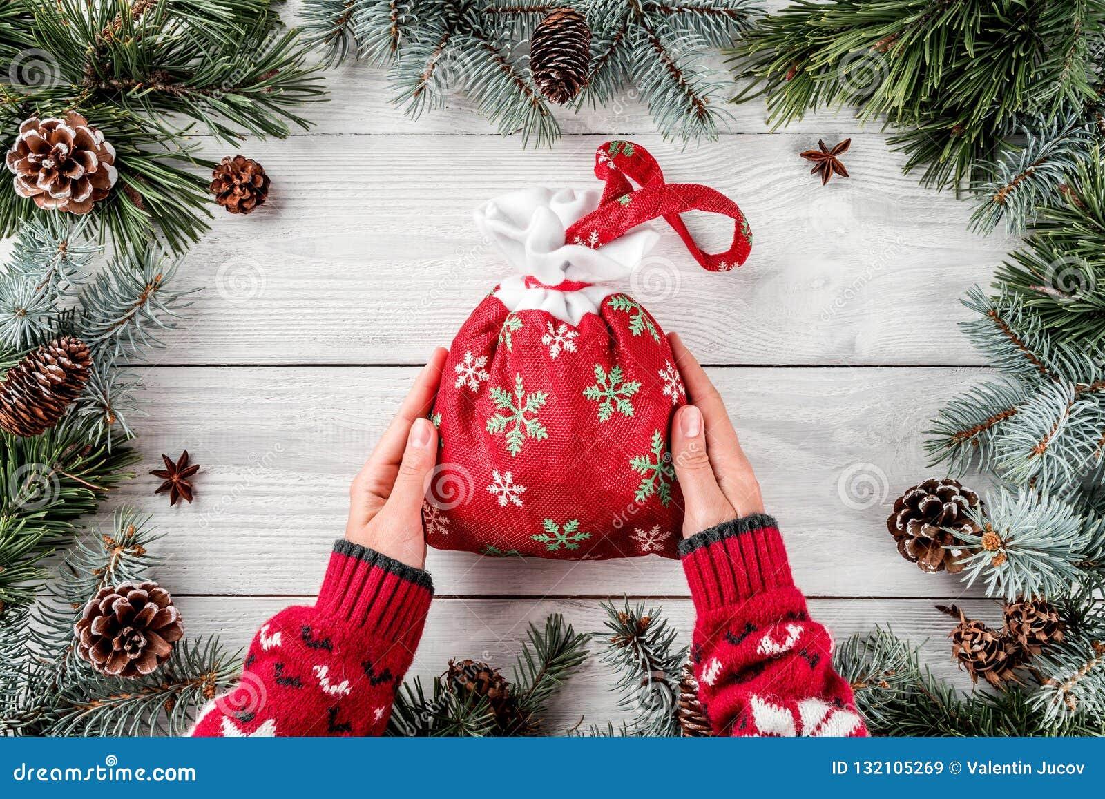Kvinnliga händer som rymmer den röda påsen för jul på vit träbakgrund med granfilialer och att sörja kottar Tema för Xmas och för