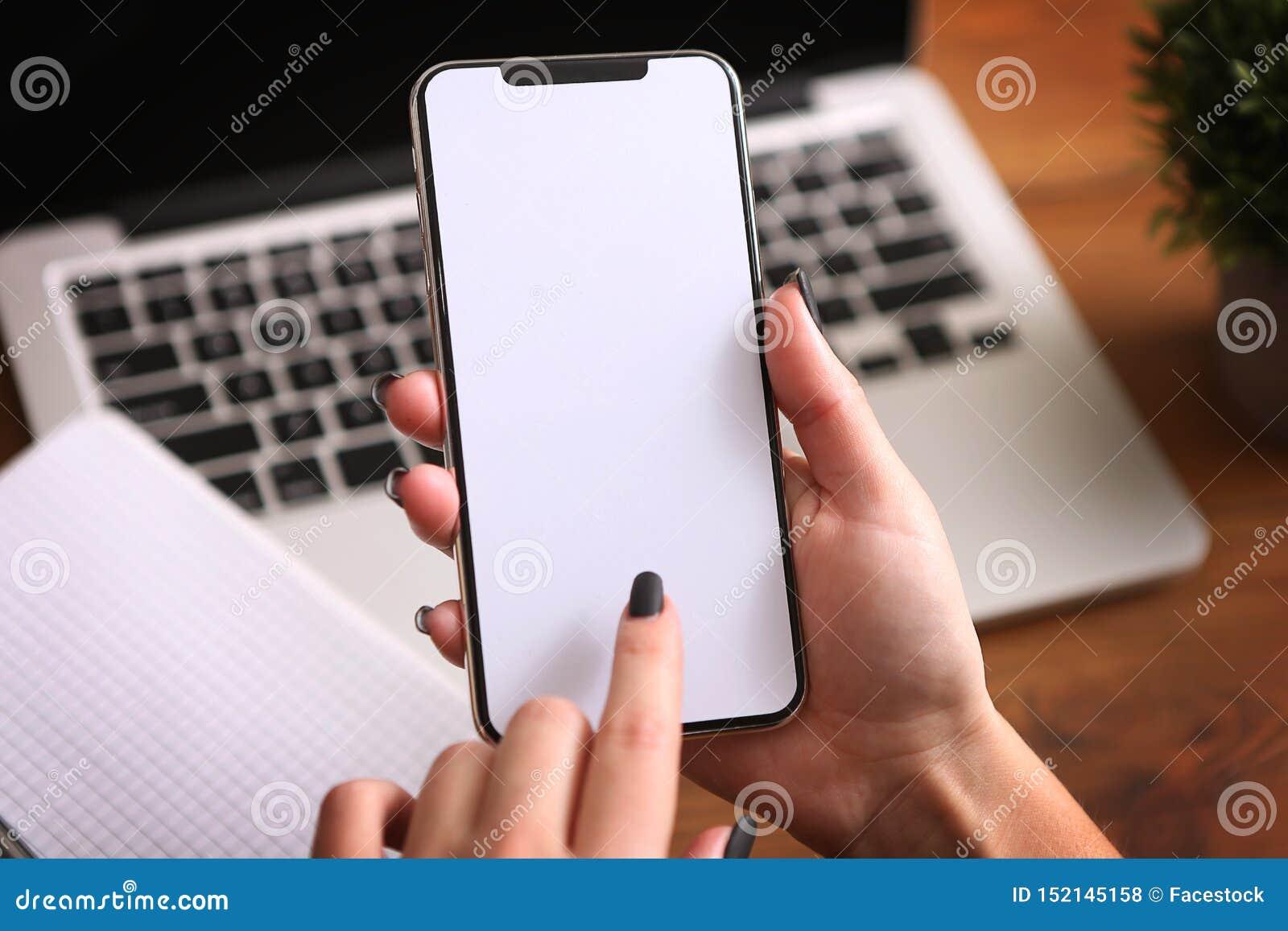 Kvinnliga händer som rymmer en vit telefon med den isolerade skärmen på en tabell med bärbara datorn