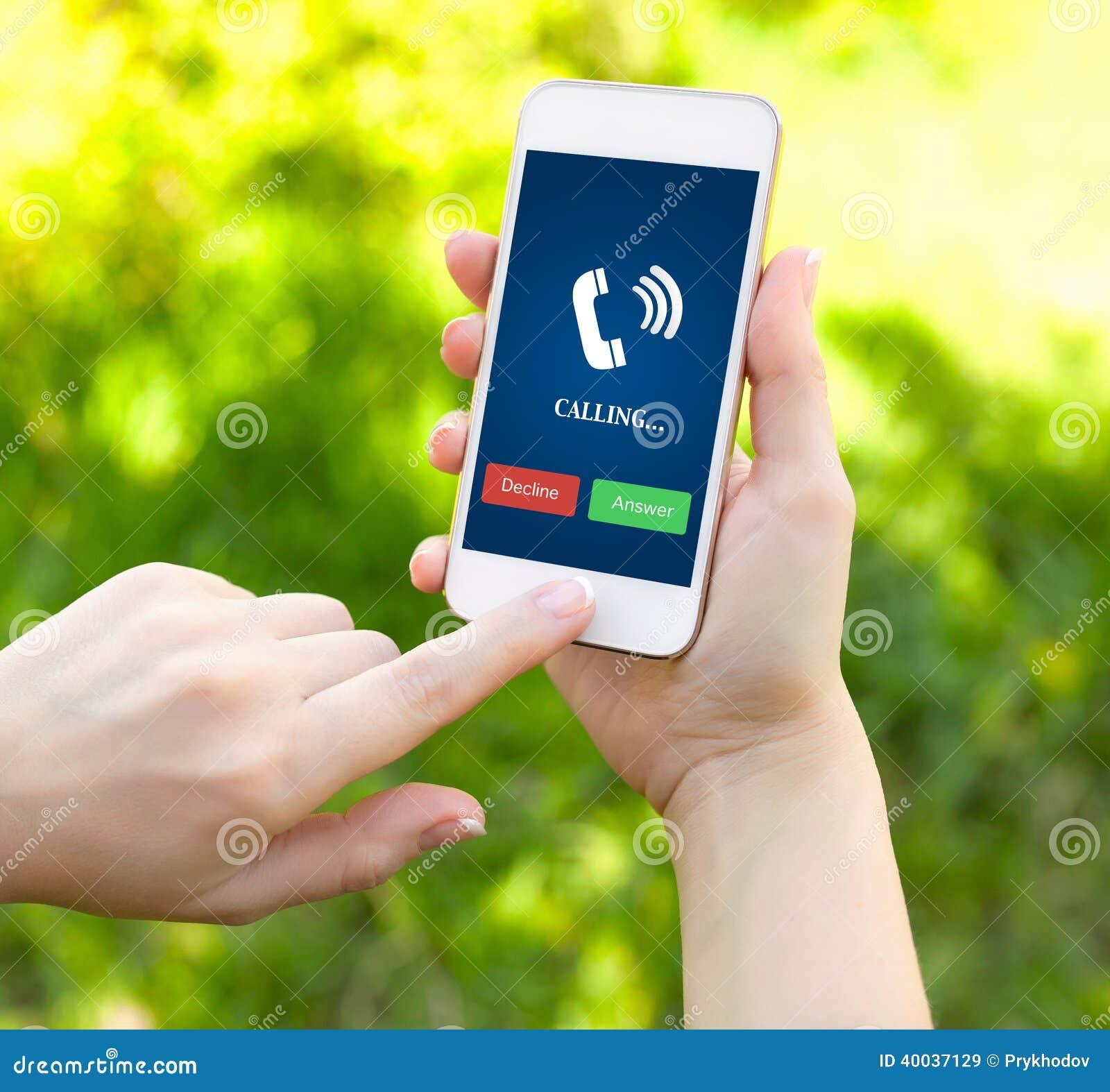 Kvinnliga händer som rymmer en vit telefon med ringningröret på scren