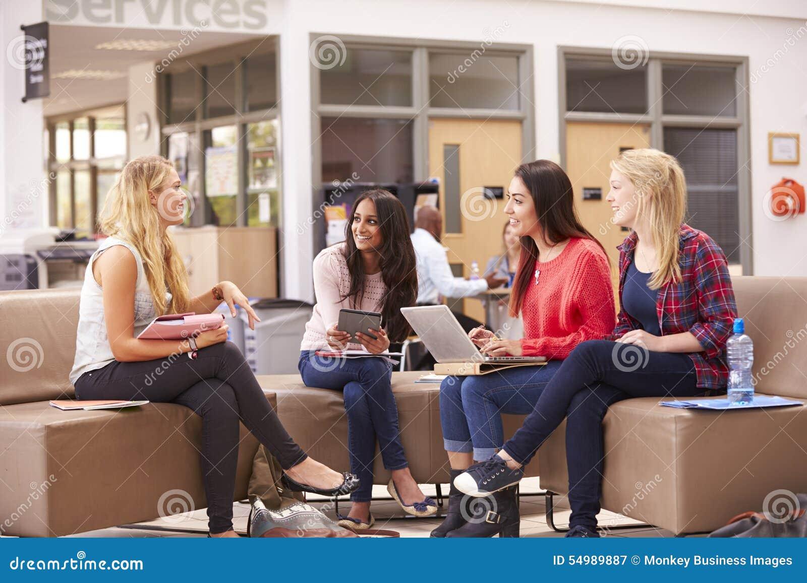 Kvinnliga högskolestudenter som tillsammans sitter och talar