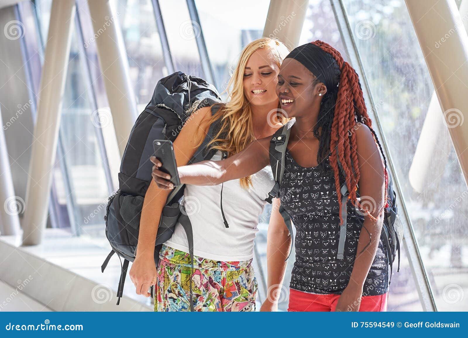 2 kvinnliga handelsresande i flygplatshallet som tar selfies