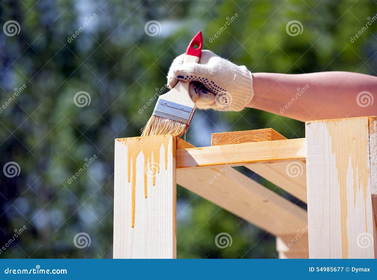 Kvinnliga handmålarfärger bryner en träcloseup för möblemang utomhus