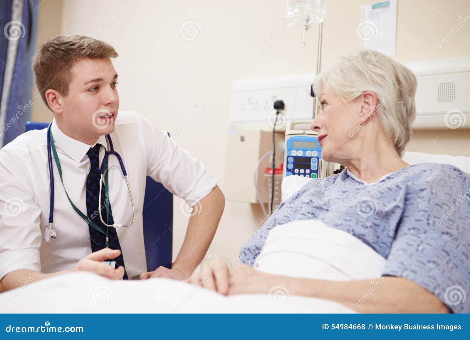 Kvinnliga patients för doktor Sitting By Senior säng i sjukhus