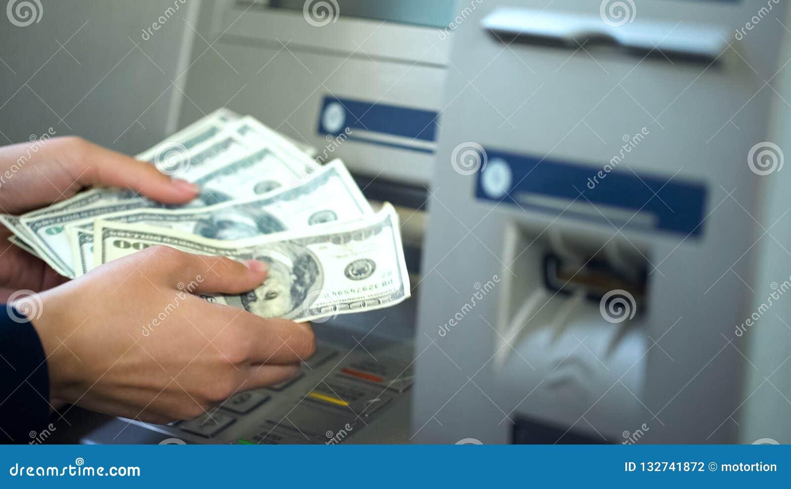 Kvinnliga räknande dollar som återtas från ATM, 24h service, lätt packa ihop operation