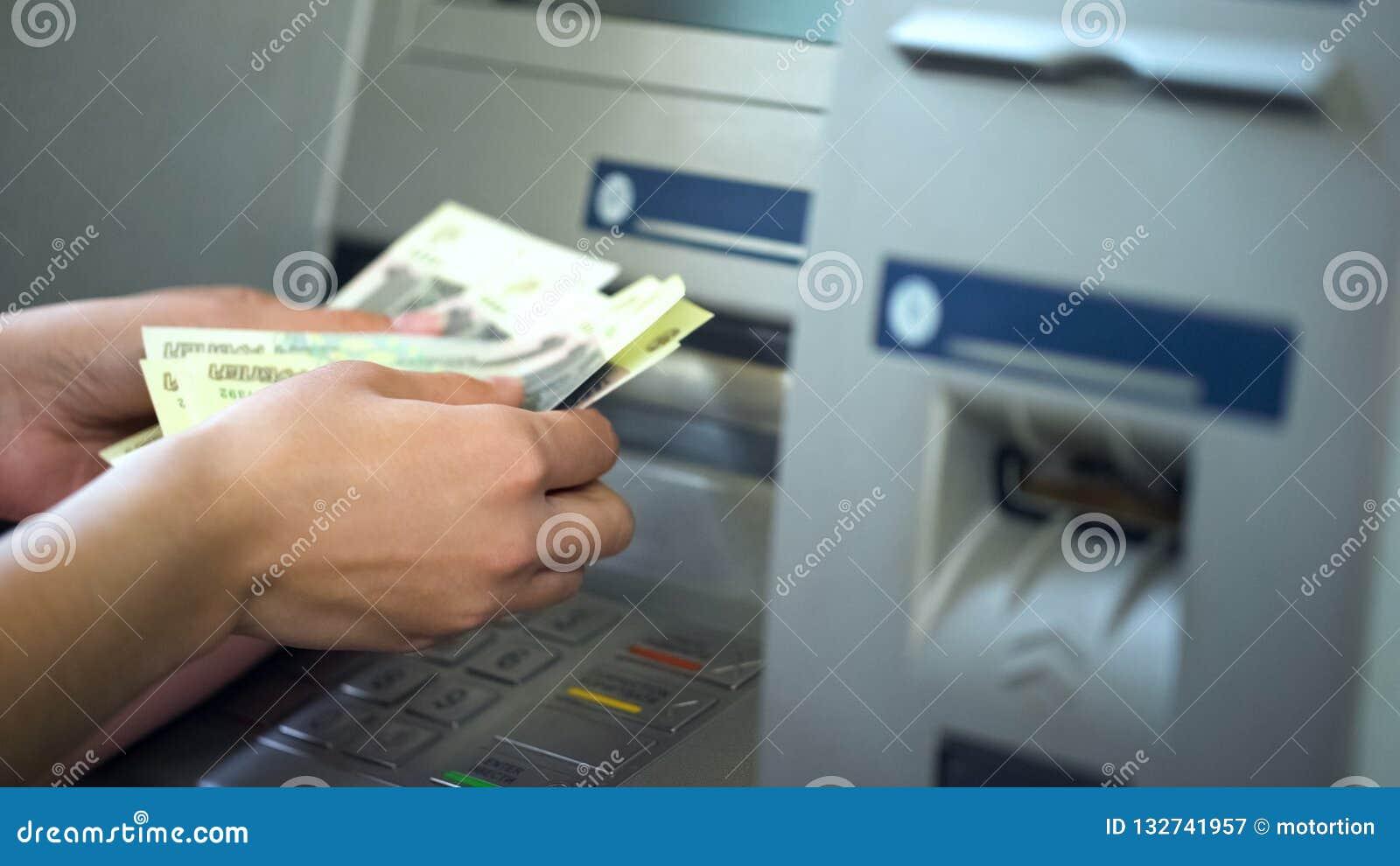 Kvinnliga räknande ryska rubel som återtas från ATM, 24h service, lätta bankrörelsen