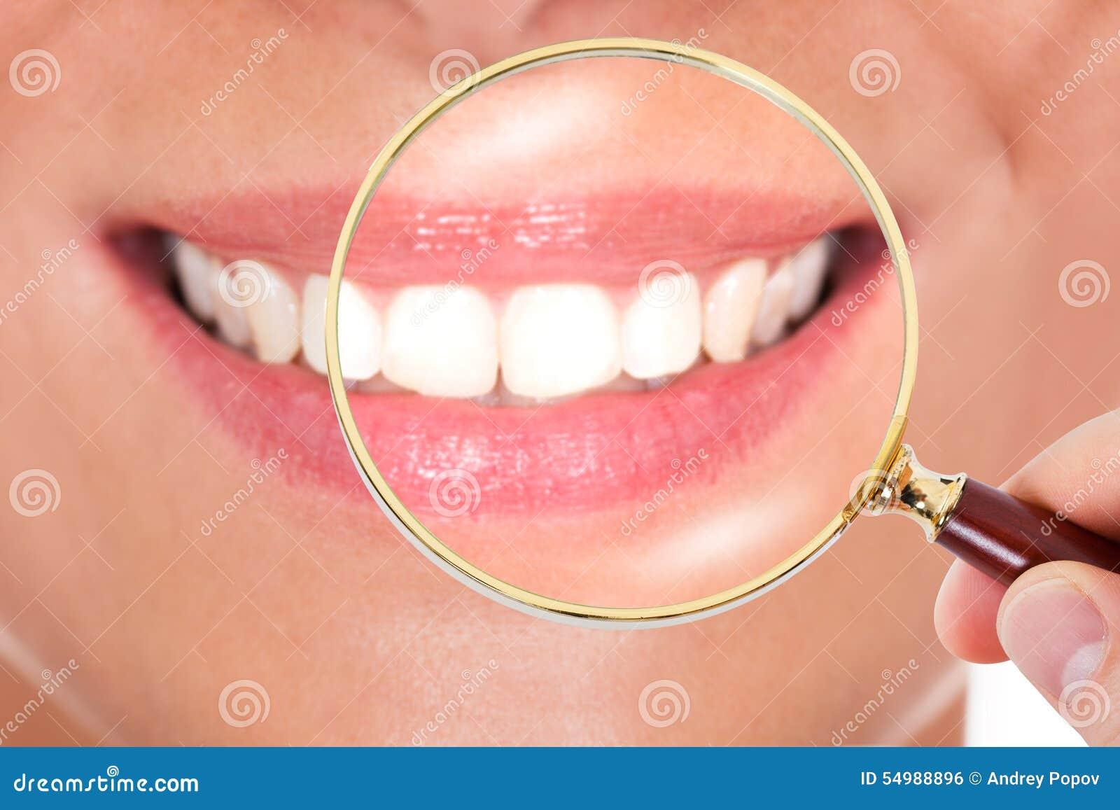 Kvinnliga tänder som kontrolleras med förstoringsglaset