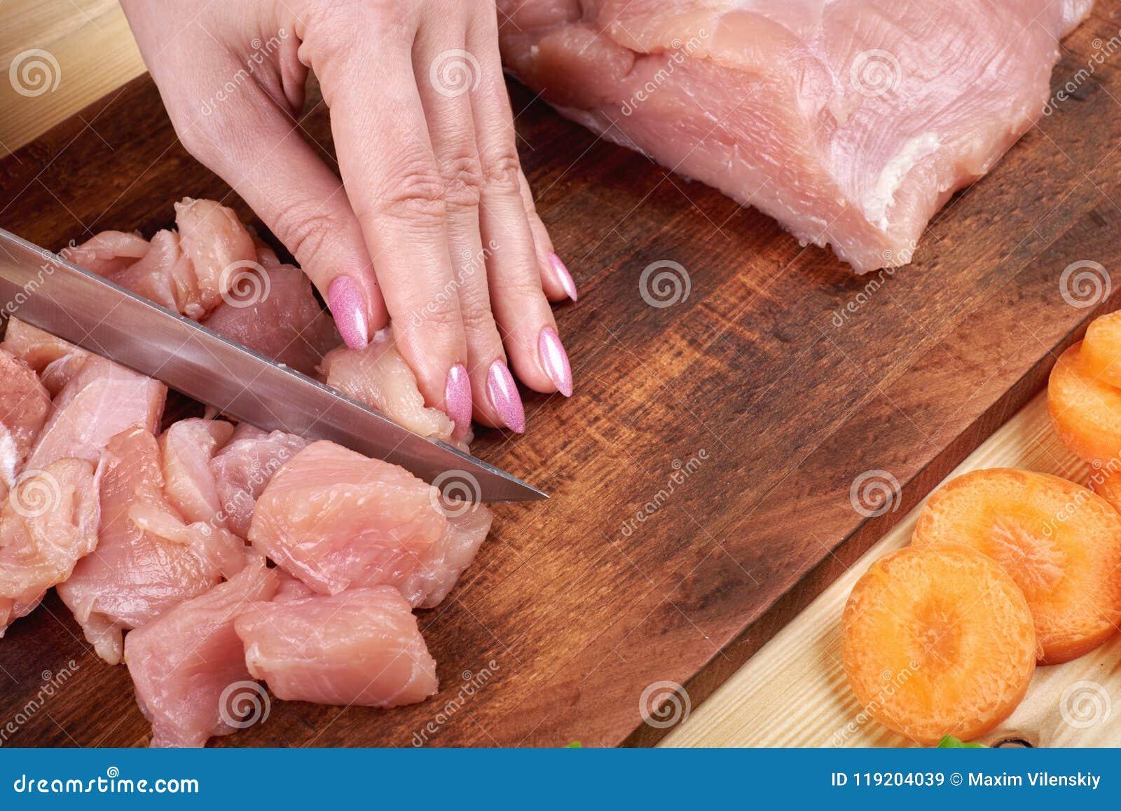 Kvinnlighänder med en kniv, snitt köttet på träbrädet Sunt äta och livsstil