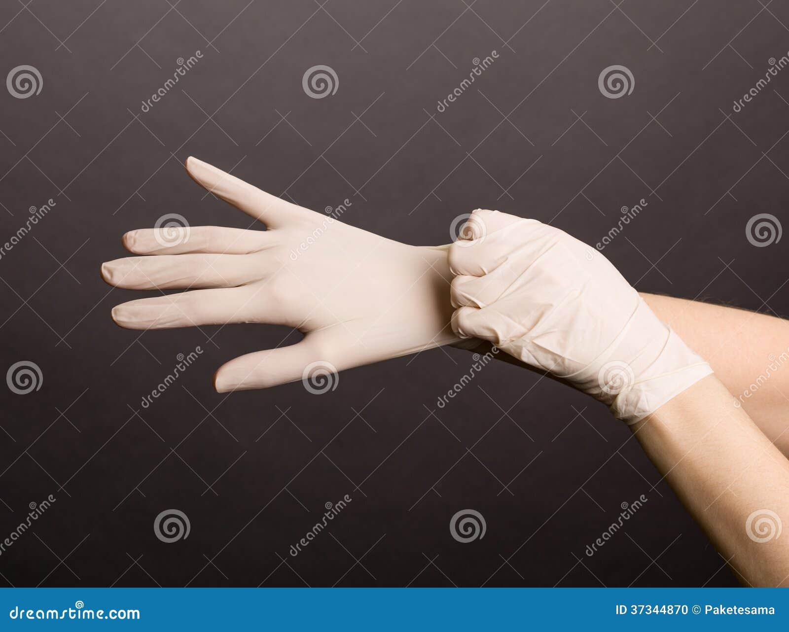 Kvinnlighänder som sätter på latexhandskar