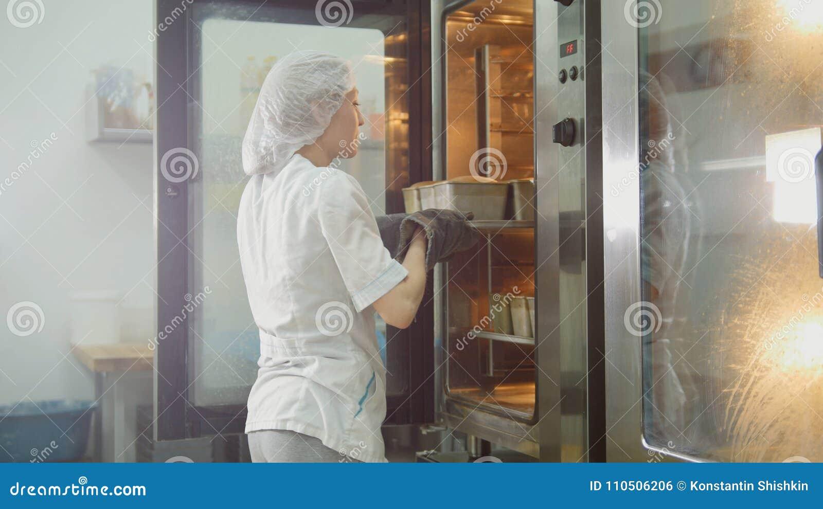 Kvinnlign bakar på kommersiellt kök - kvinnan sätter bakning i ugnen