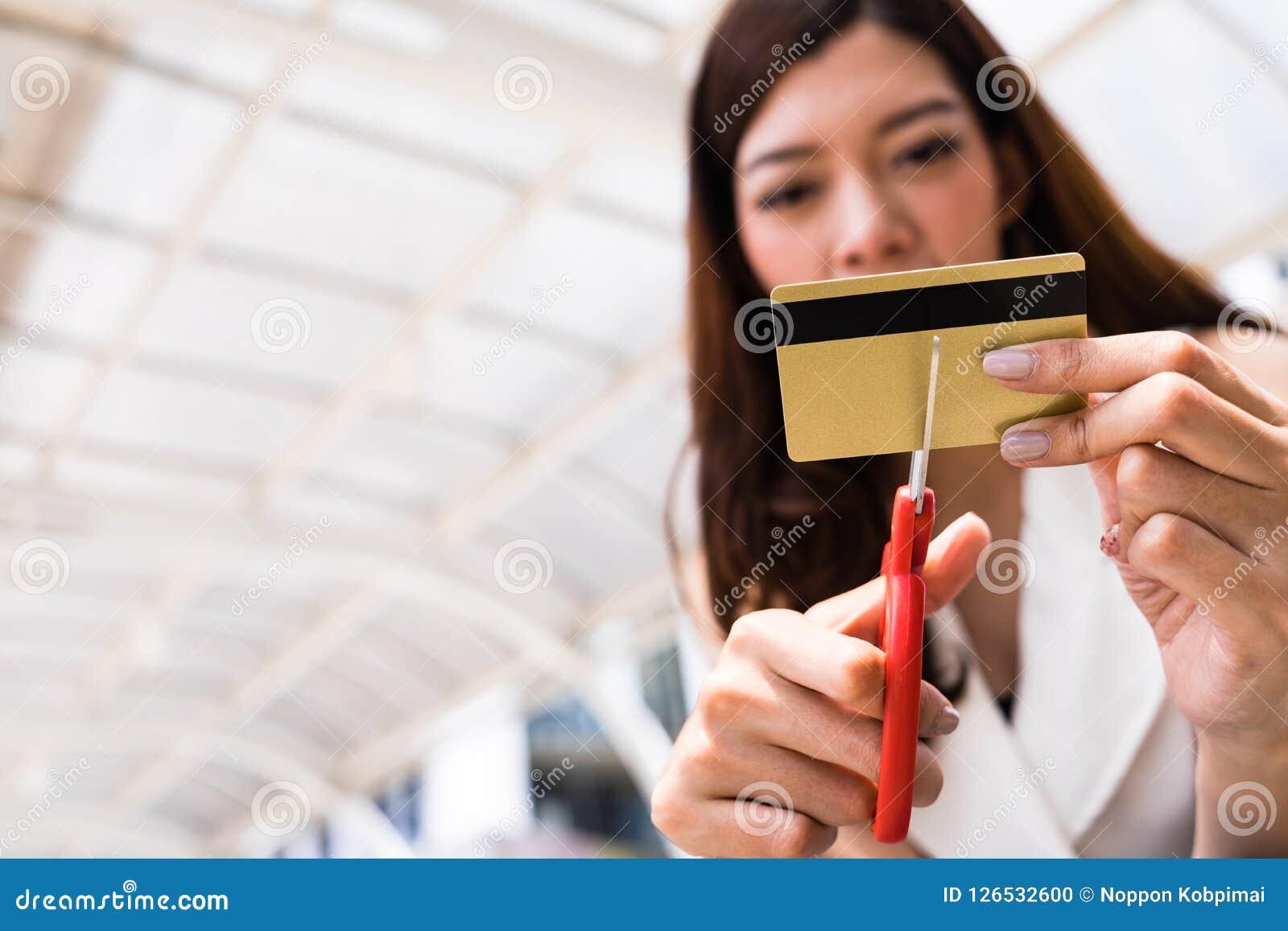 Kvinnlign räcker den bitande kreditkorten med sax