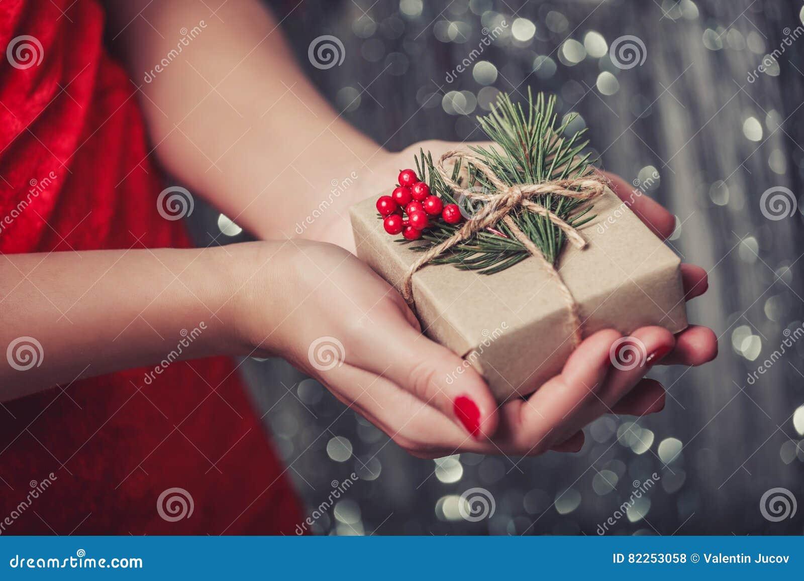 Kvinnlign räcker den hållande julgåvaasken med filialen av granträdet, skinande xmas-bakgrund Feriegåva och garnering
