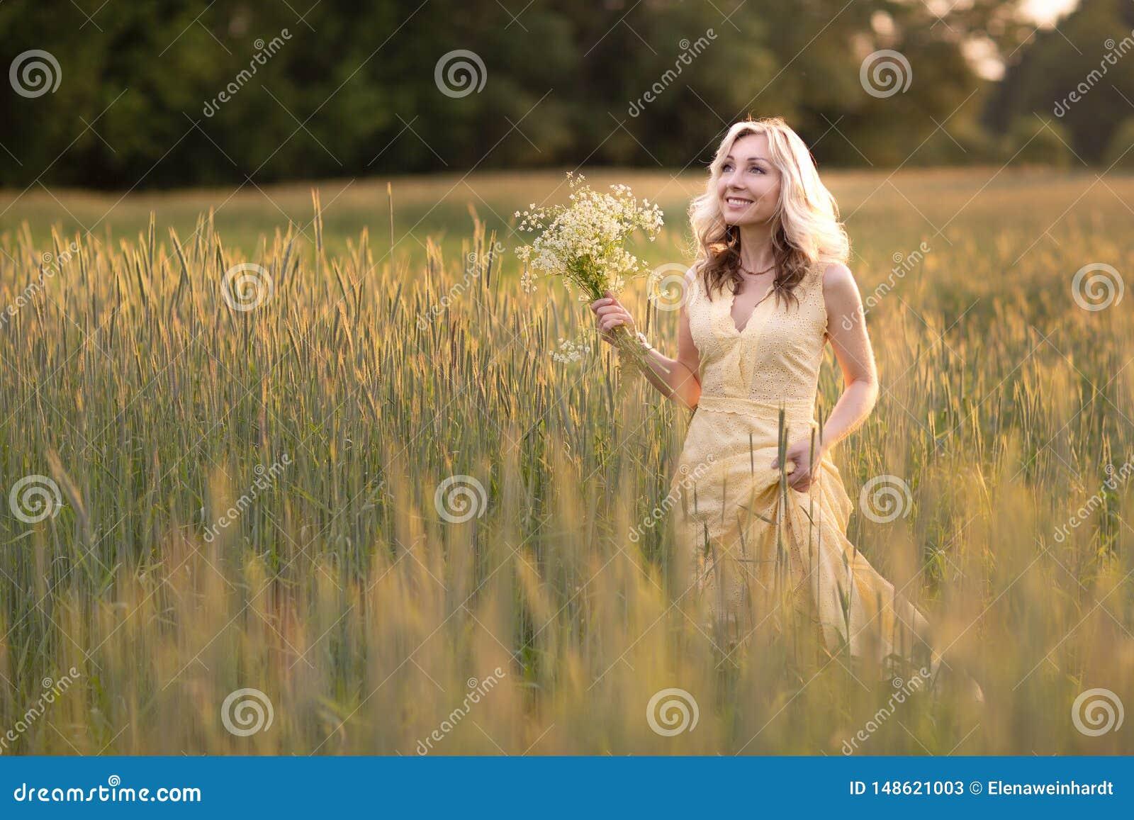Kvinnligst?ende utomhus Solnedg?ngkvinna i ett f?lt med en bukett av l?sa blommor