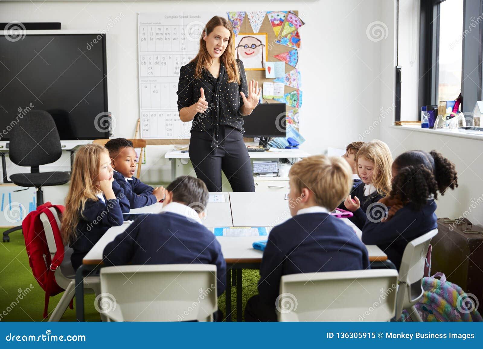 Kvinnligt anseende för skolalärare i ett klassrum som gör en gest till skolbarn som sitter på en tabell som lyssnar